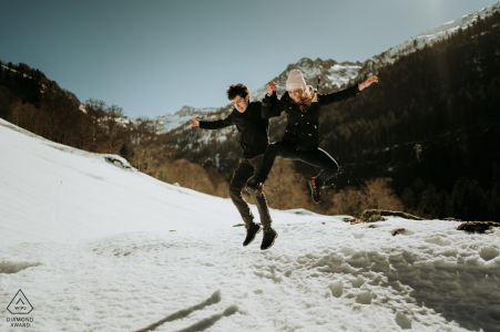 FR engagement photo shoot in Pyrenees France with a couple jumping in the winter snow