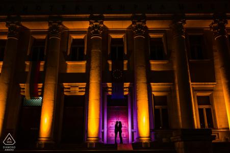 Séance photo de fiançailles BG de nuit devant les Sts. Bibliothèque nationale Cyrille et Méthode à Sofia, Bulgarie montrant deux amoureux devant les colonnes de la bibliothèque