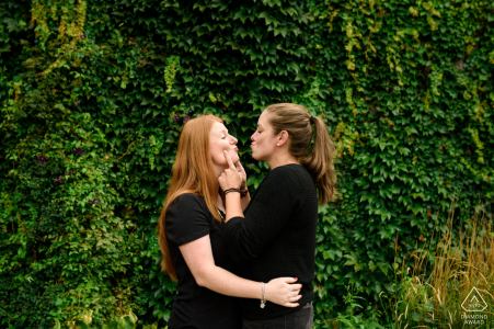 Quebec pre wedding and engagement photography in Parc Jean-Drapeau, Montreal of a couple hugging and making silly kissy faces against a wall of green vines