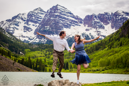 CO pre-wedding photo session with an engaged couple jump as high as they can, hand in hand, with the towering Maroon Bells peaks behind them in Aspen, Colorado