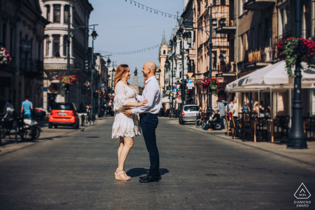 PL engagement photoshoot & pre-wedding session on Piotrkowska Street as the two hold hands in Lodz, Poland