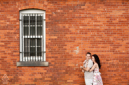 RI engagement photo shoot of a couple in front of brick wall and window iin Newport, Rhode Island