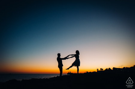 PT pre-wedding photo session with an engaged couple dancing during the sunset in Caxias beach, Lisboa, Portugal
