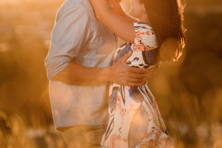 Australia pre wedding and engagement photography in Fossil Bluff, Tasmania, Australia of a couple in the long grass bathed in golden hour light