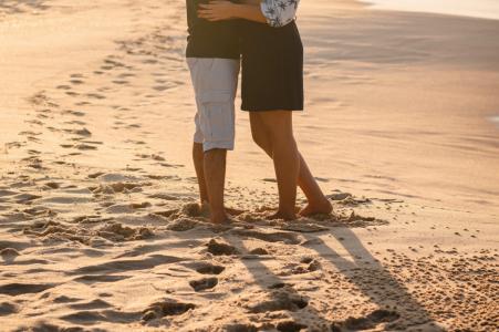 Brasilianisches Verlobungsporträt mit einem posierten Paar, das auf dem Strandsand von Niteroi - RJ Brasilien steht, wenn die Sonne ein beleuchtetes Bild küsst