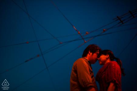Séance photo de fiançailles NoCal à San Francisco avec Le couple éclairé contre le ciel bleu crépusculaire