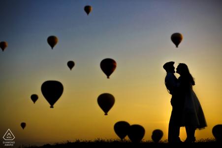 Séance photo d'engagement en Turquie au lever du soleil alors que les montgolfières prennent leur envol au-dessus de la Cappadoce, Turquie