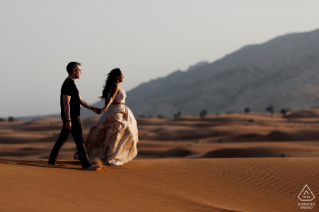 UAE pre-wedding photo session with an engaged couple at Fossil Rock, Dubai Desert while Walking on the edge of the dunes