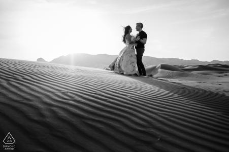 Portrait de fiançailles des Émirats arabes unis avec un couple posé dans les sables chauds de Dubaï tout en dansant dans le désert
