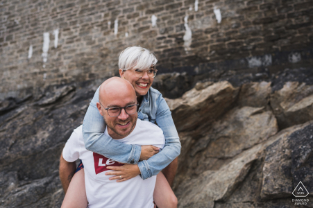 FR pre wedding portrait session with engaged lovers riding piggy back in Saint Malo, France