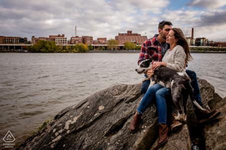 DC pre sesión de retrato de boda con amantes comprometidos colgando sobre las rocas junto al agua en Roosevelt Island, Washington DC