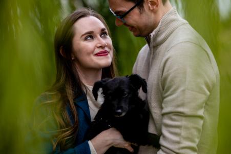 Distrito de Columbia fotografía previa a la boda y el compromiso en Washington DC de una pareja abrazada con su cachorro bajo un sauce
