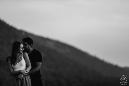 Sesión de fotos de compromiso de Nevada en Lake Tahoe que muestra a una pareja abrazándose ante un telón de fondo de montaña en blanco y negro
