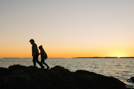 Lighthouse Point Park, New Haven, Connecticut couple walks together holding hands over a black rocky formation as the sun sets behind them over the ocean