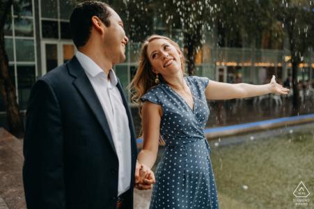 Texas couple ayant leur moment heureux lors de leur séance de fiançailles avec une pluie soudaine au centre-ville de Houston