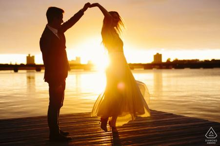 Charles River Engagement Session avec couple dansant au coucher du soleil sur le quai au bord de l'eau