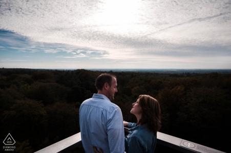 Dans le Kaapse Bossen à Doorn Le couple est debout sur une tour de guet qui s'élève au-dessus des arbres lors d'une séance photo pré-mariage