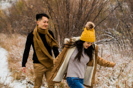 Lair O Bear Park Couple walking through snow during a winter engagement pre-wed photo session