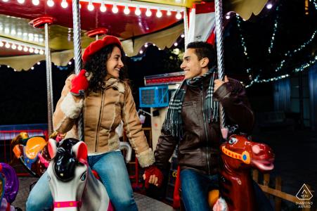 Jaén Pre-Wedding portraits with a couple riding horses on a fair carousel