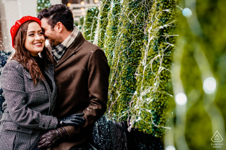 London, United Kingdom couple in love in snowy London by green shrubs for their pre-wed portrait photography session