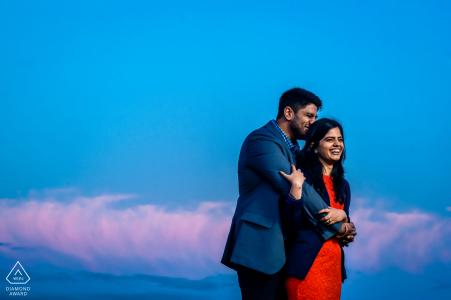Primrose Hill, Londres couple debout au sommet de la colline avec ciel bleu et rose au cours d'une séance photo portrait pré-mariage