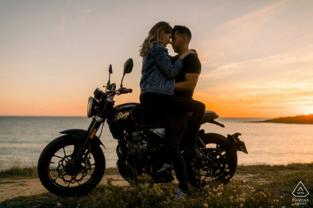Les Sables d'Olonne, Vendee, France Silhouette pre-wed shot of a couple kissing at sunset on a motorbike over the ocean