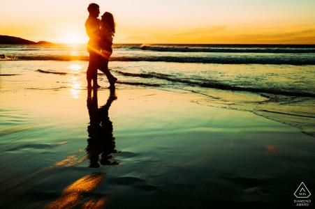 Llandudno Beach, Cape Town séance de photographie de plage avant le jour du mariage avec une silhouette créative au coucher du soleil de l'heureux couple engagé sur la plage