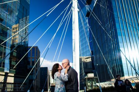 Mini-Urban-Fotoshooting in Denver, Colorado vor dem Hochzeitstag mit einem Paar, das sich einen Knutschfleck auf der Millennium Bridge teilt