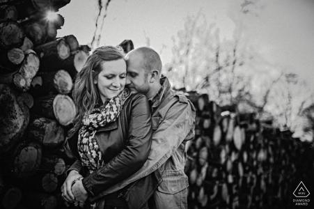 Hampshire Woods mini séance photo de couple avant le jour du mariage à côté de bois de chauffage coupé et empilé