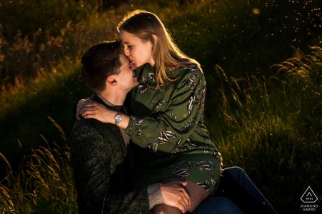 Centre Willemstad mini séance photo avant le jour du mariage - couple dans un champ d'herbe avec un baiser dans le beau coucher de soleil