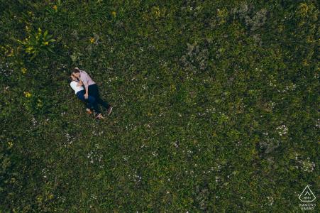 Mini sesión de fotos de compromiso de Crested Butte antes del día de la boda con la pareja tendida en un campo