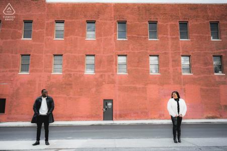 Seviervile, TN Mini Urban Bild vor dem Hochzeitstag erstellt als Das Paar lächelt sich an, als sie vor einem alten Backsteingebäude in der Innenstadt von Sevierville stehen