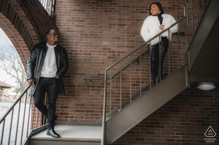 Sevierville, TN, mini sesión de fotos urbanas antes del día de la boda mientras la pareja se mira mientras están parados en unas escaleras en el centro de Sevierville.