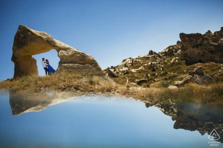 Capadocia, Turquía mini sesión de fotos de pareja antes del día de la boda con un reflejo del amanecer en el espejo en las rocas