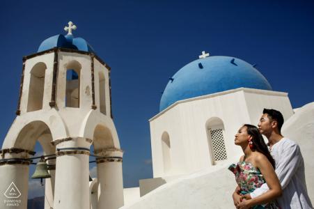 Santorin, Grèce mini séance photo de couple avant le jour du mariage contre les bâtiments blancs aux toits bleus et un ciel bleu