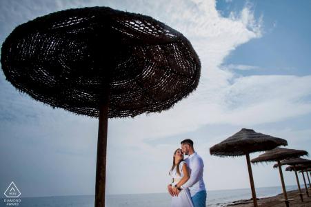 Aguilas, Espagne mini séance de photographie de couple de plage avant le jour du mariage avec un peu d'amour à la plage sous les parasols