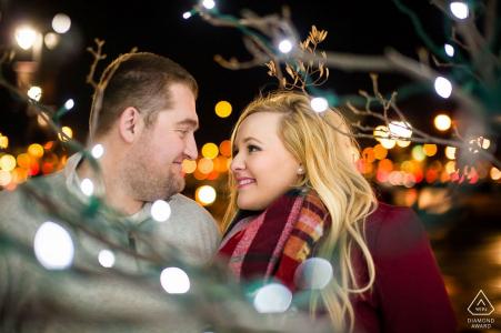 Fargo, Dakota du Nord, mini séance photo de couple avant le jour du mariage avec un regard les uns sur les autres car ils sont entourés de lumières de Noël la nuit