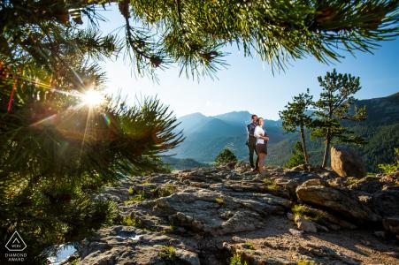 Estes Park, Colorado, een fotoshoot voor een paar in de bergen, gedaan terwijl de zon ondergaat achter de rotsachtige bergen, het paar poseert voor een verlovingsportret.