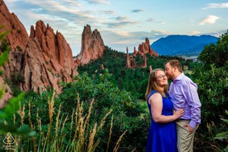 Portret van een paar in Colorado Springs, terwijl hij zijn verloofde een knuffel op de wang geeft voor het ongelooflijke zomerse uitzicht op Garden of the Gods.