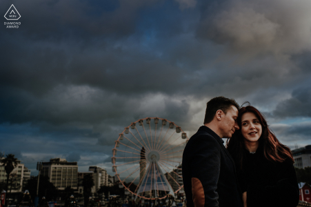 Parque Eduardo VII couple portrait of the two enjoying the end of the day with a view a big wheel in Lisbon