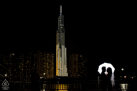 Ho Chi Minh City urban pic shoot before the wedding day with a lit umbrella and the night city skyline