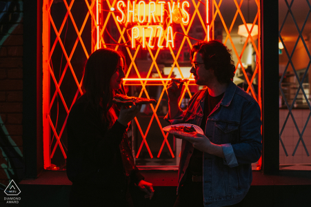 Hamilton, Ontario couple pre-wed portrait at Shorty's Pizza displaying a young couple celebrating the end of their engagement session with a few slices of pizza by the glow of the neon lights