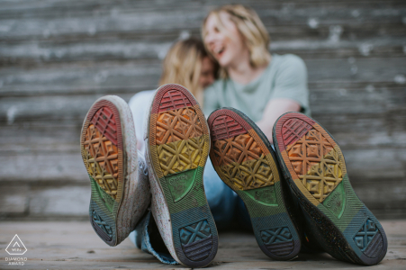 Toronto couple engagement pic session with Two women madly in love cuddle in the background with the focus on their shoes, the soles a rainbow