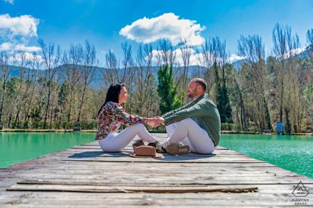 Séance photo engagement couple Jaen à l'hôtel Noguera de la Sierpe à Arroyo Frío sur le quai en bois au bord de l'eau, assis et se tenant la main