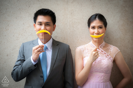 Bangkok couple pre-wed portrait at Siam Kempinski with a snack which is a pickled mango with a skewer that looks cute to bring it action, the groom's mustache and the bride's smile