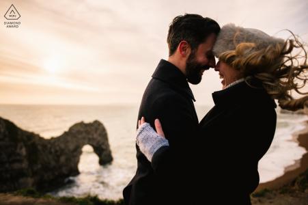Durdle Door, Dorset, coppia di fidanzati, sessione fotografica sulle scogliere ventose che si affacciano sull'arco di roccia sul mare