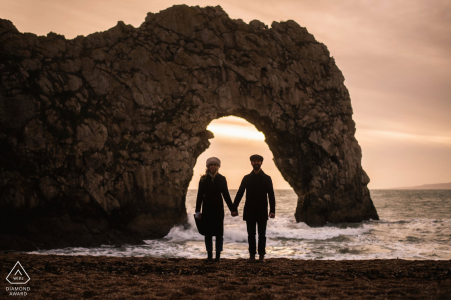 Dorset couple engagement pic session at Durdle Door with isolated framing in the arch doorway