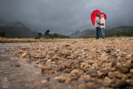 Rocky Mountain National Park Fine Art Engagement Image pour un couple sous le parapluie du cœur un jour de pluie au bord d'une rivière dans une grande vallée