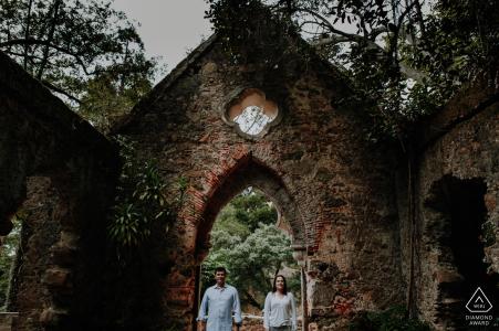 Sesión de fotos previa a la boda de Sintra con estilo de bellas artes en Lisboa, PT de una pareja encuadrada frente a una capilla en ruinas