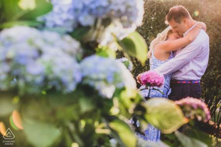 Nantucket, MA portrait e-session du couple partageant une étreinte avec des fleurs au premier plan
